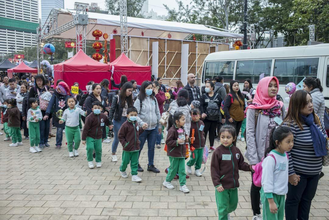 根據香港法例,外籍傭工不得在港從事家務勞動以外的工作,也就是說外傭照顧家中兒童事屬本職,但「照顧」的邊界可有限定? 圖為年宵市場外,不少外傭手拖僱主的小孩。