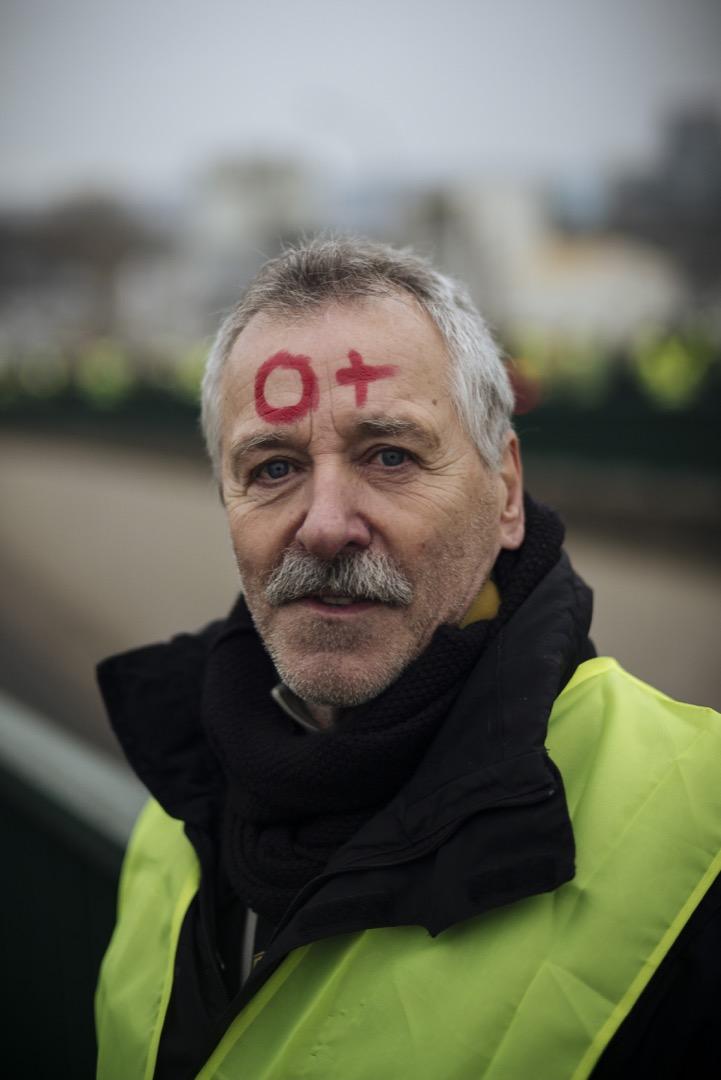 退休人士,66歲的Jean-Michel在額頭上寫上自己的血型O+,以抗議防暴警察對待示威者的暴力手段。