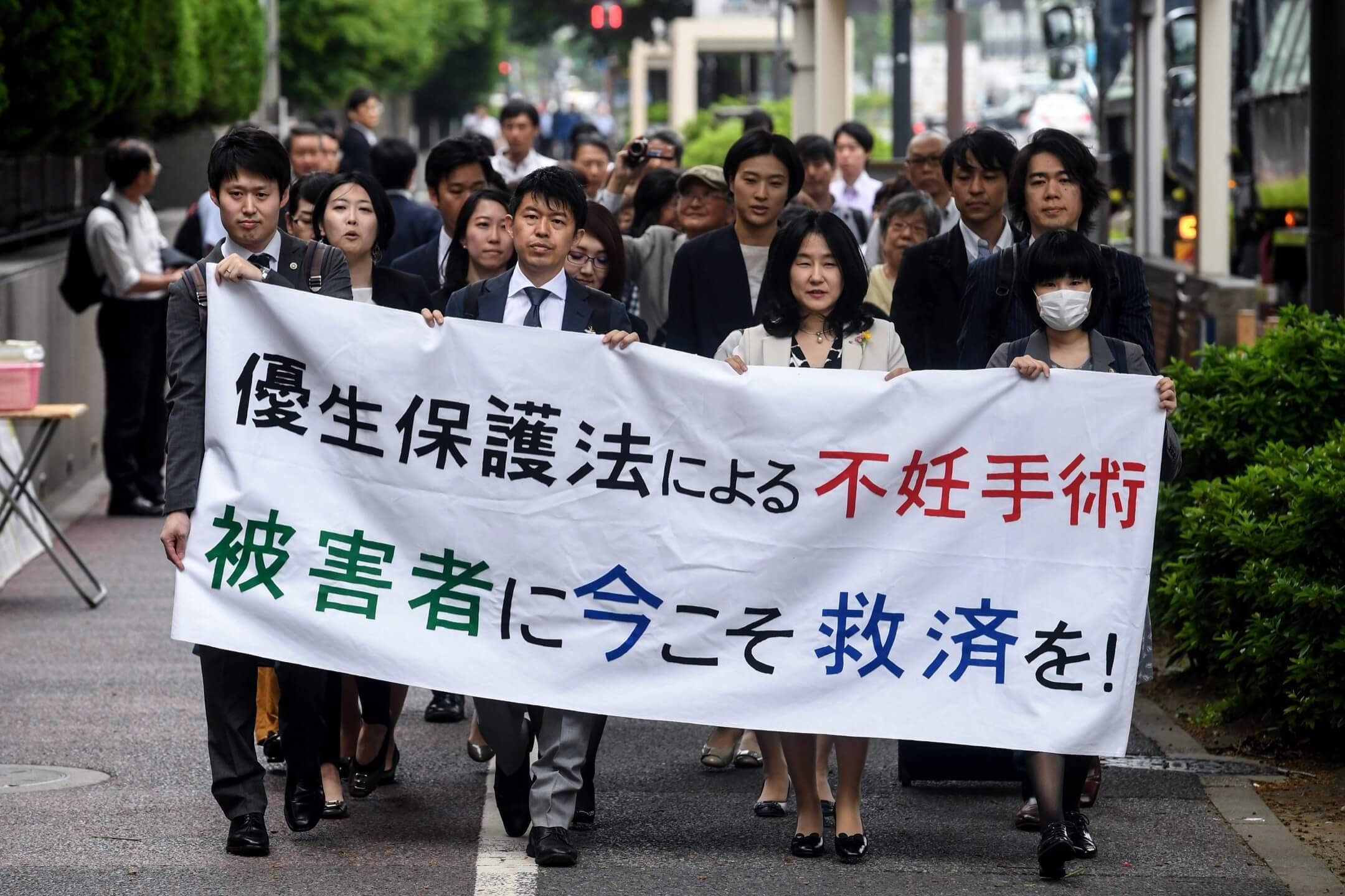 2018年5月,律師團和支持者們手持標語遊行到東京地方裁判所,要求被強制絕育的受害者得到賠償。 攝:Toshifumi Kitamura/AFP/Getty Images
