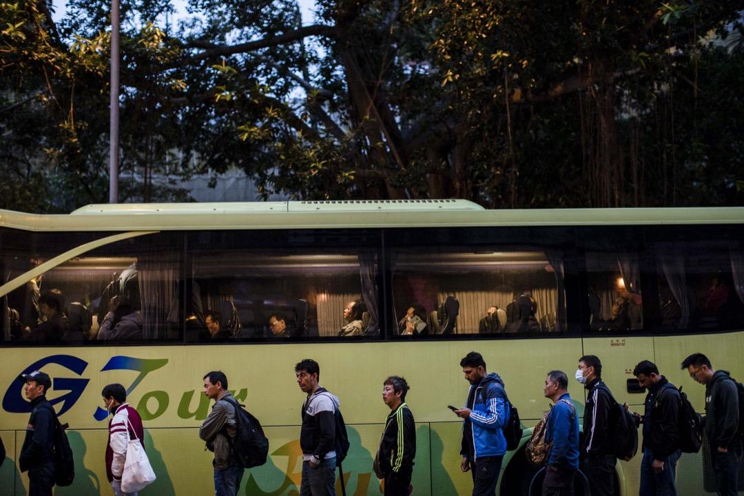 3月1日清晨,工人們如常到裕民坊遊憩公園外,等候來接送他們到地盤工作的旅遊巴士。
