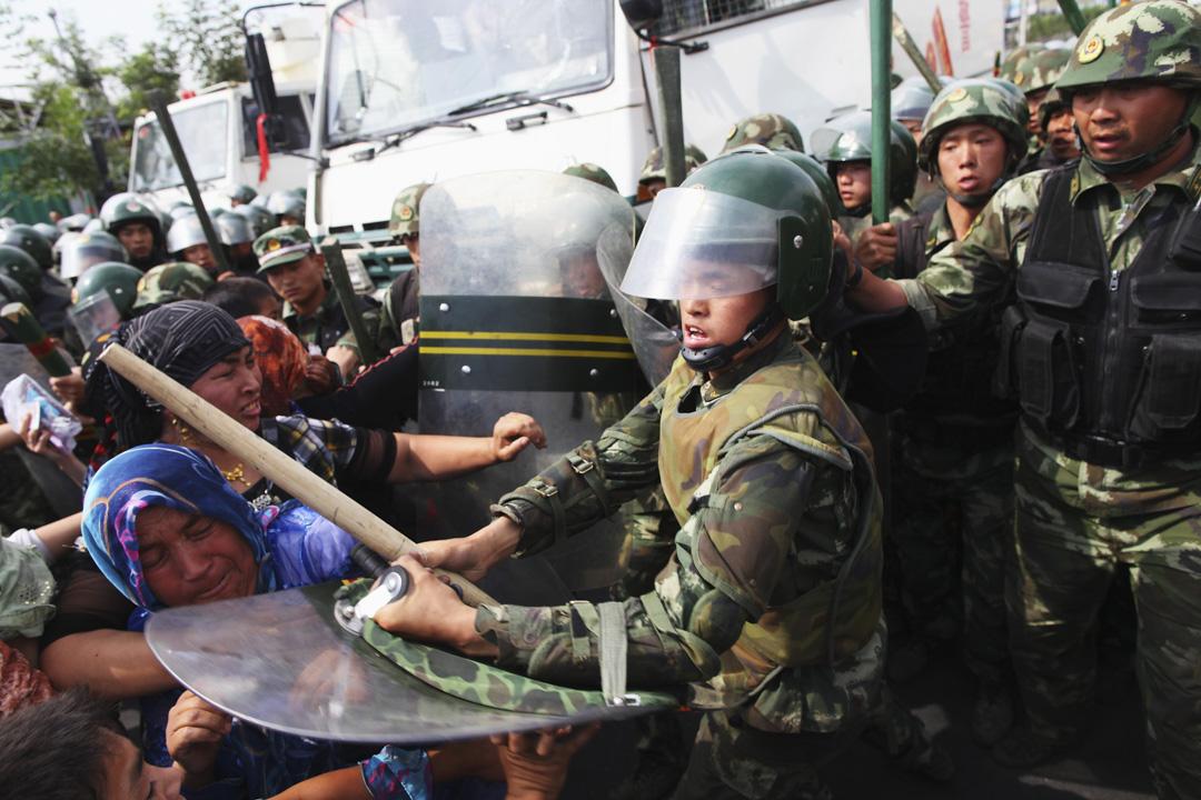 2009年7月7日,新疆烏魯木齊,維吾爾族婦女於街頭抗議後遭軍警驅趕。