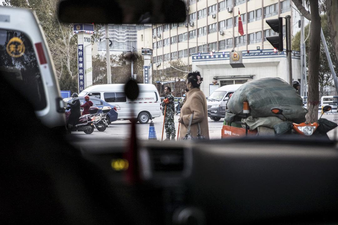 """2018年11月8日,新疆喀什的一個""""便民警察局""""前的一個交叉路口,有一個穿著迷彩服及拿著棍子的男士。 攝:Bloomberg"""
