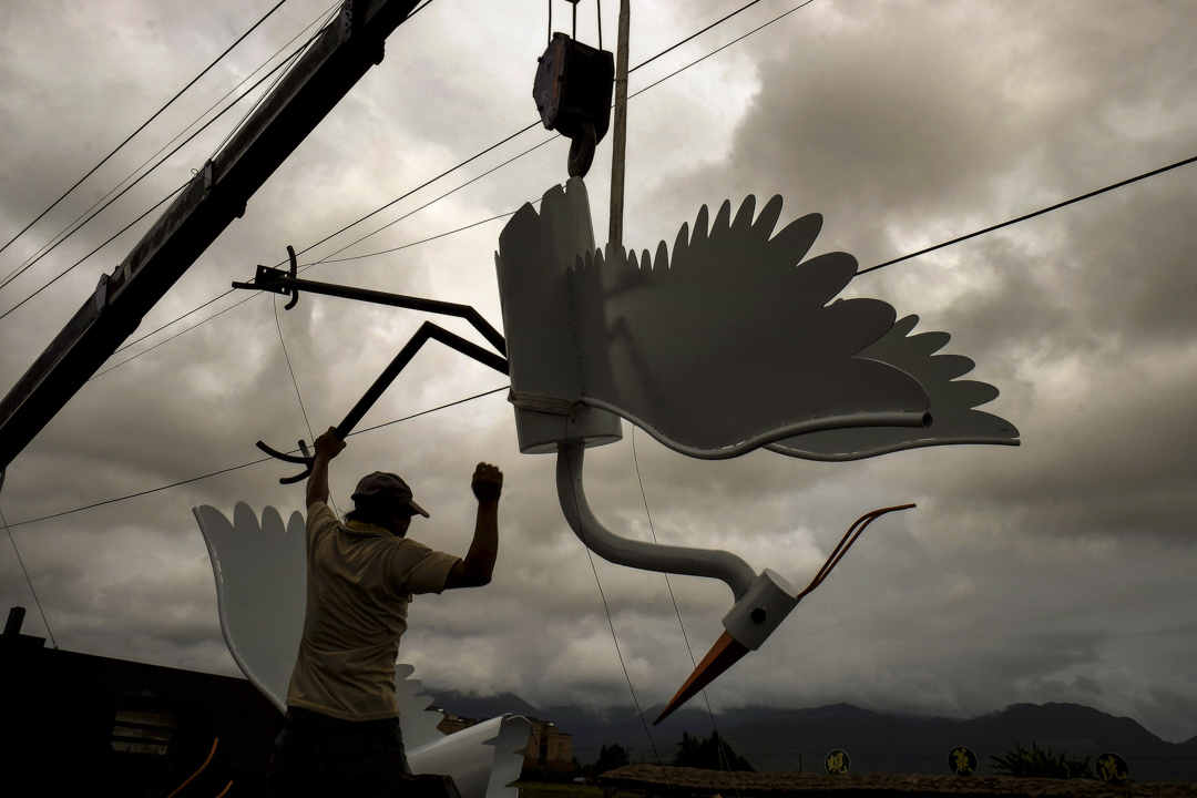台東一名農民在颱風來臨前取下起重機。