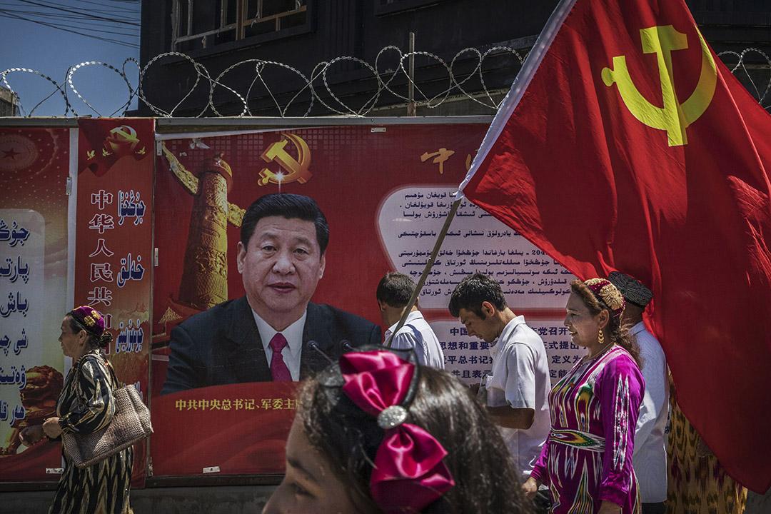 2017年6月30日,在新疆喀什老城區,一班共產黨維吾爾族成員經過中國國家主席習近平的海報 。 攝:Kevin Frayer/Getty Images