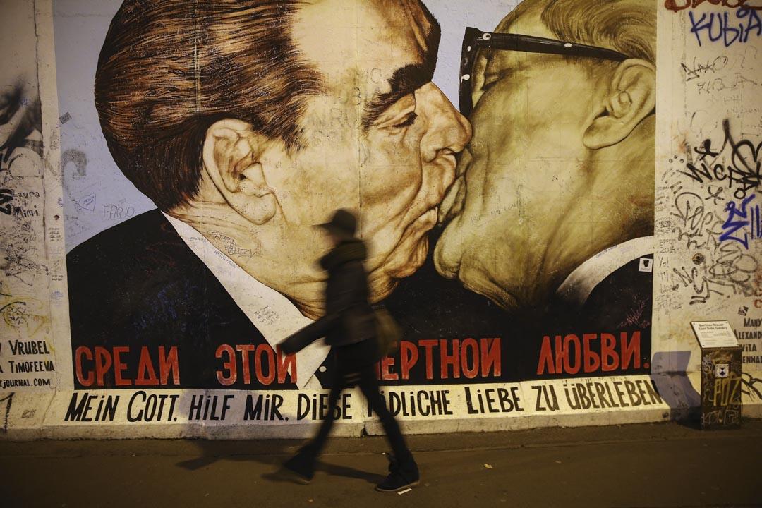 一位遊客走過一幅柏林圖牆一幅壁畫,展示前蘇聯領導人勃烈日涅夫親吻前東德共產黨領袖何內克。