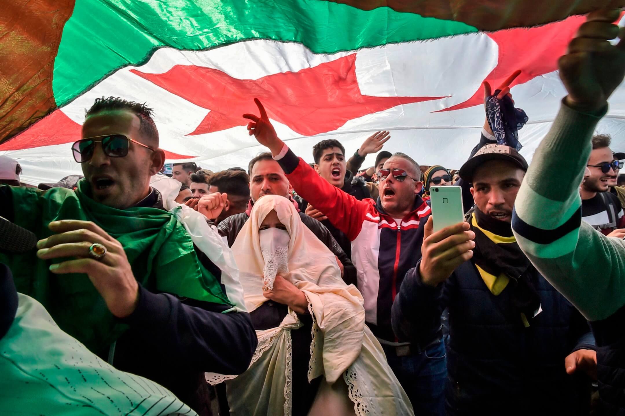 2019年3月1日,阿爾及利亞首都阿爾及爾,民眾在街頭揮動國旗示威,抗議現任總統布特弗利卡第五度角逐連任總統。 攝:Ryad Kramdi/AFP/Getty Images
