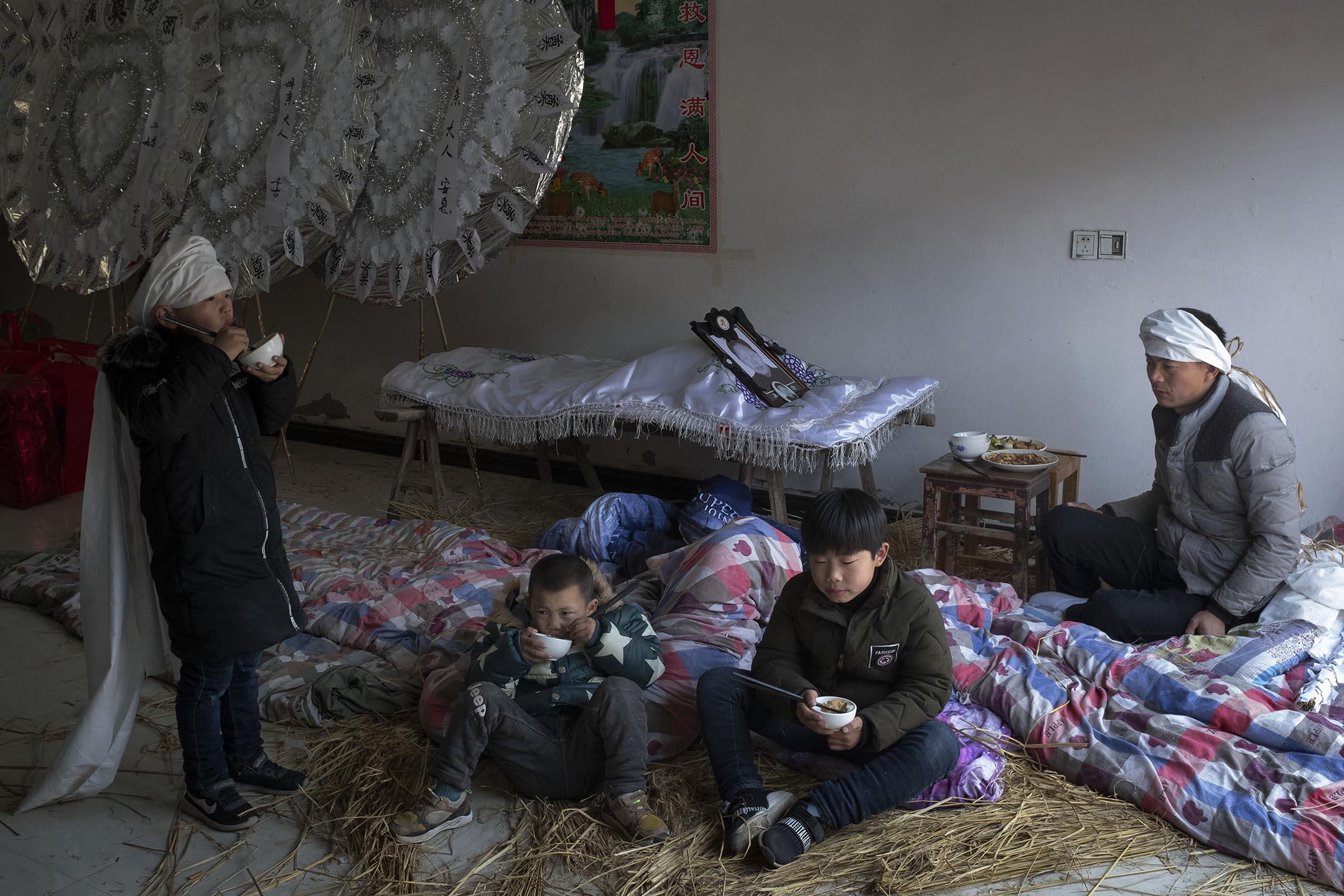 陳家港六港村舉行喪禮,兒子正為爆炸時在家壓死的母親守靈。