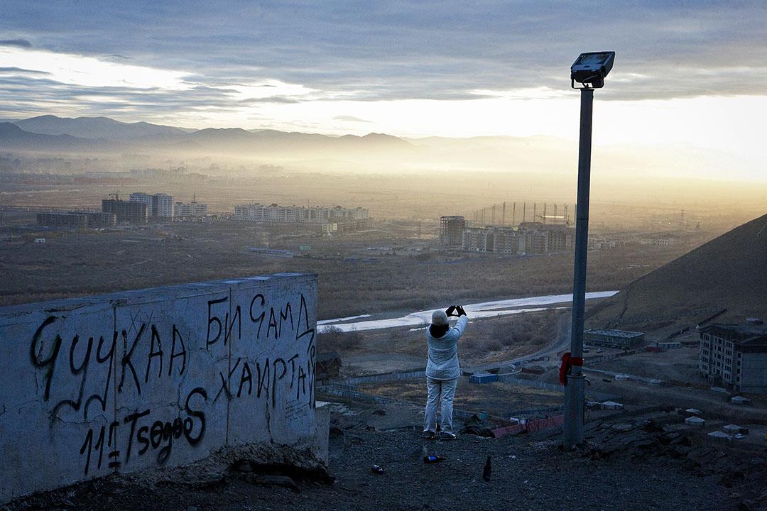 一個女人在山頂俯瞰烏蘭巴托市。