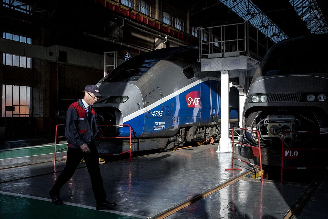 2017年10月26日,法國貝爾福的Alstom工廠的機庫內,一名員工經過TGV高速鐵路列車。