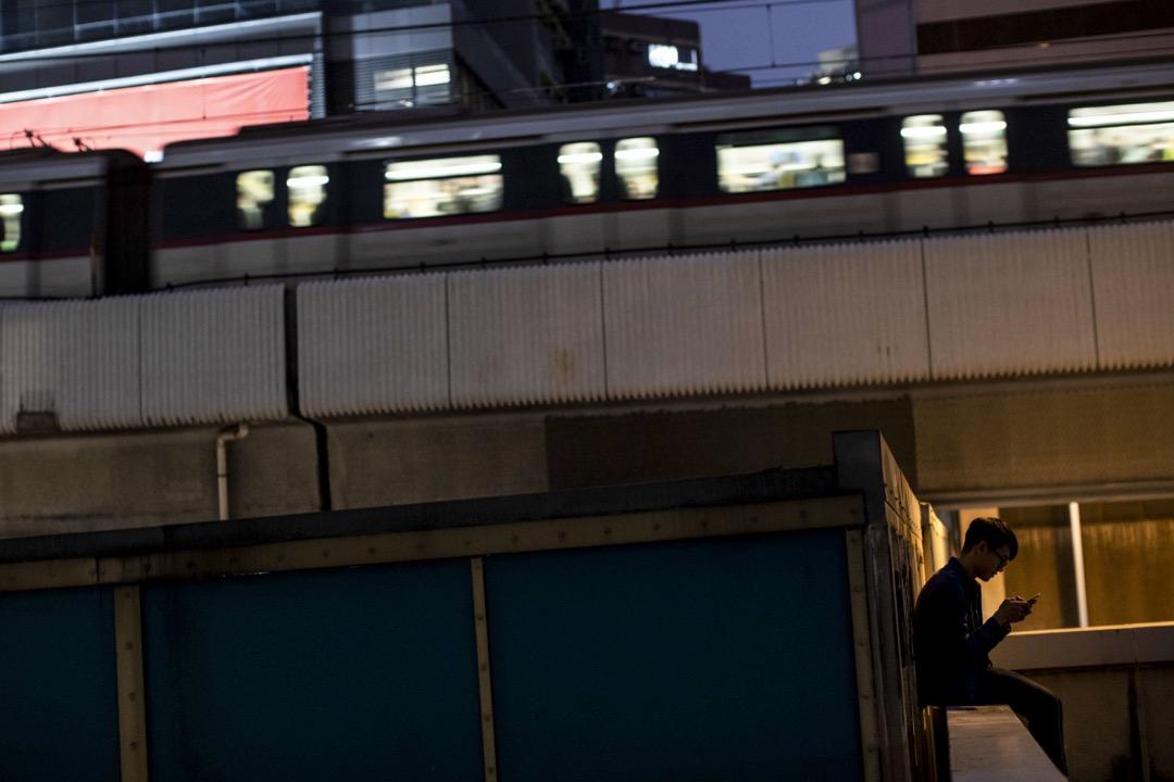 一名少年在裕民坊的平台玩手機,一列地鐵在後面的一段架空鐵路駛過。