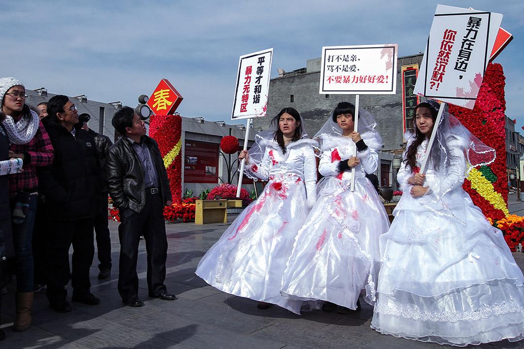 2012年2月14日情人節,三名女孩在北京市街頭穿上血淋淋的婚紗,為家庭暴力受害者抗議,左為李麥子,右為韋婷婷。