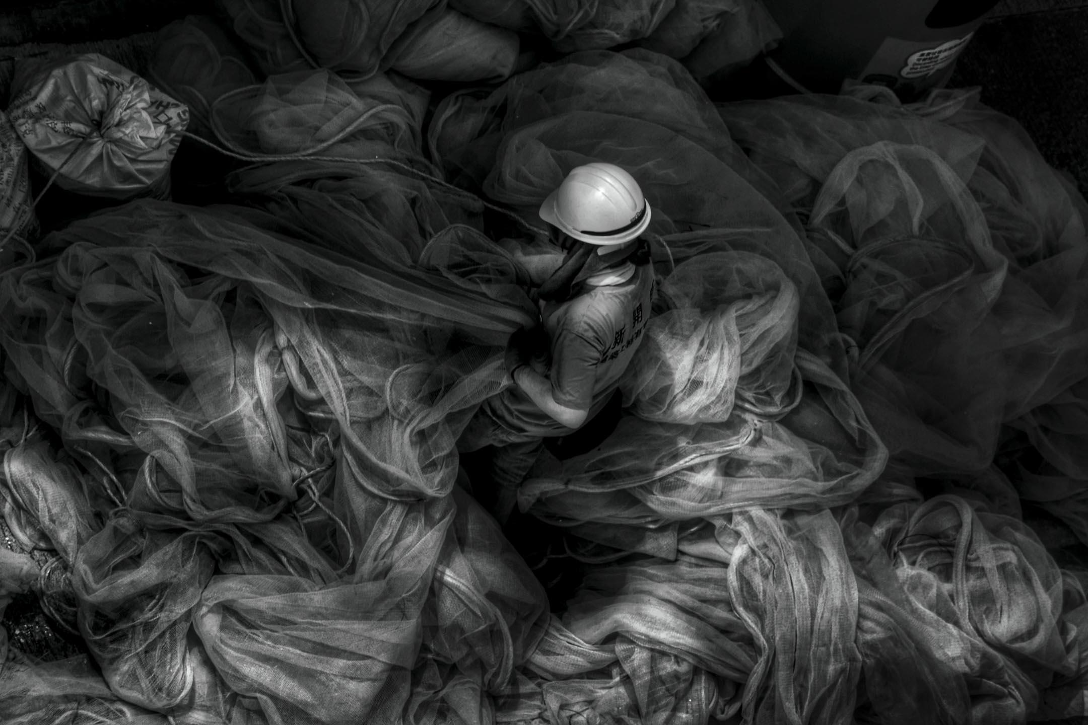 《奉獻》Sacrifice,炎夏、汗水、安全網與工人;每一刻,默默勞力的人,付出有許多。Joan Pabona於僱主八樓的家中望向窗外,捕捉到這一刻。此作品獲「2017年國家地理會德豐青年攝影大賽」「香港人和事」組別第二名。 攝影:Joan Pabona