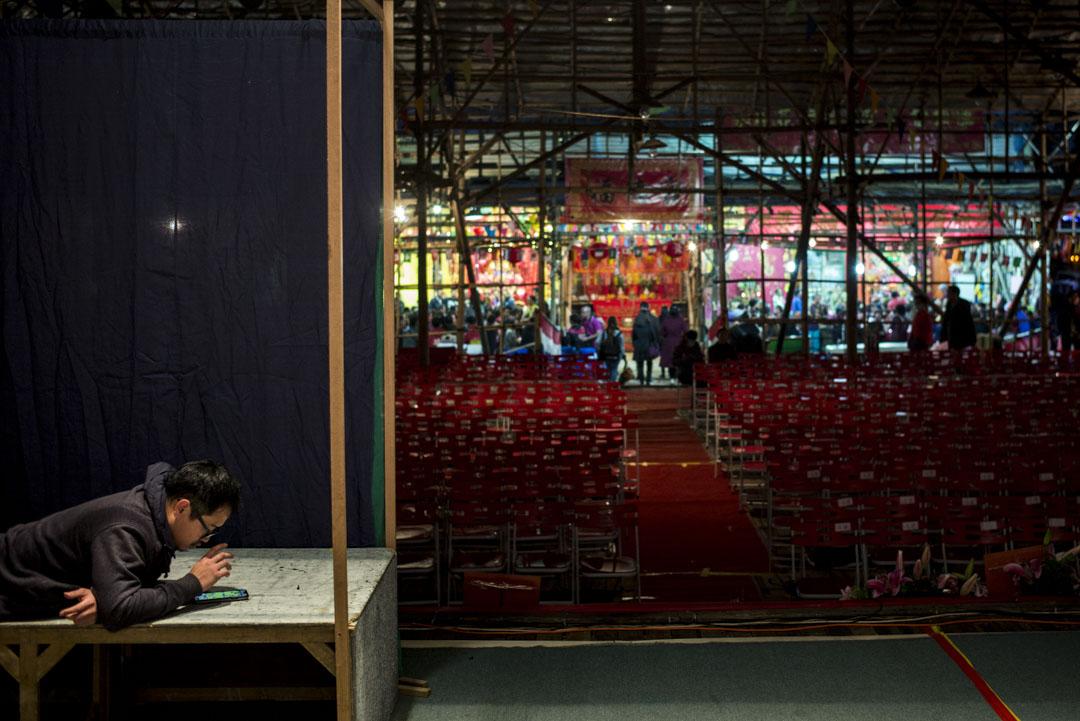 工作人員在準備中的舞台佈置上稍事休息。