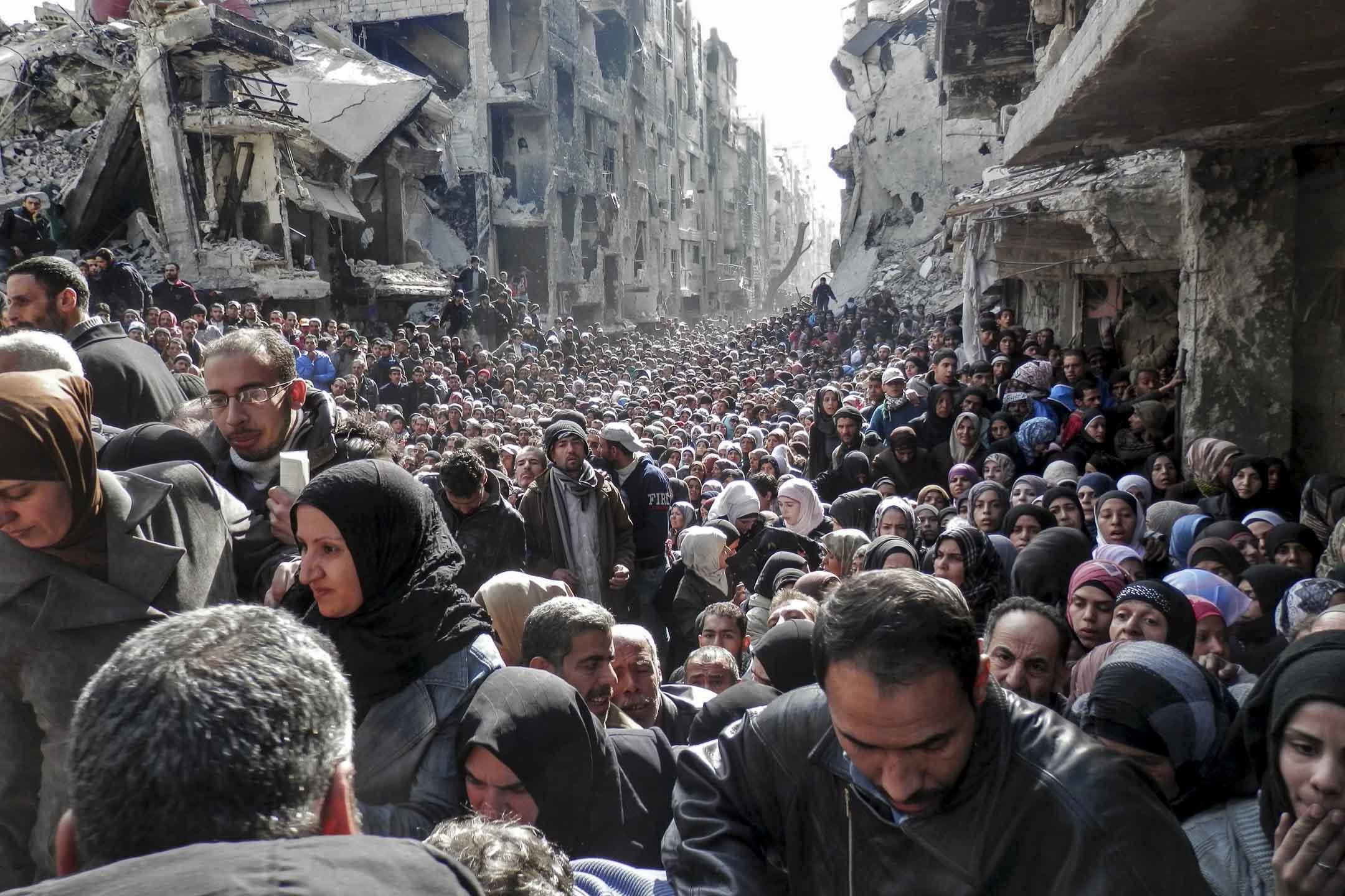 敘利亞的八年內戰,600多萬人在境內流離失所,近600萬人逃離國境,引發當代最嚴重的難民潮。圖為2014年1月31日,敘利亞大馬士革居民排隊等候難民營分發糧食援助。  攝:United Nation Relief and Works Agency via Getty Images