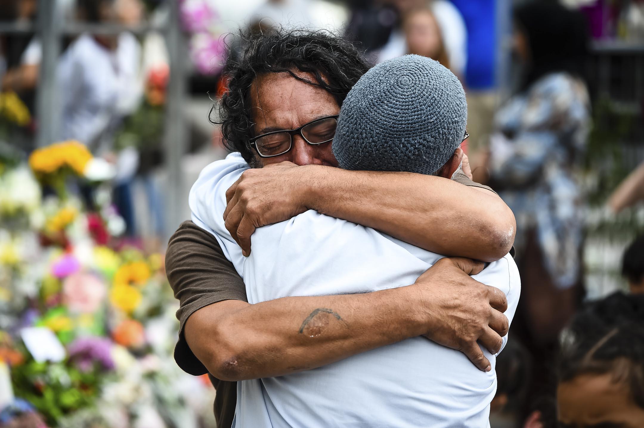2019年3月17日,發生新西蘭槍擊案的清真寺現場,有民眾獻花悼念遇難者,期間有出席者傷心擁抱。