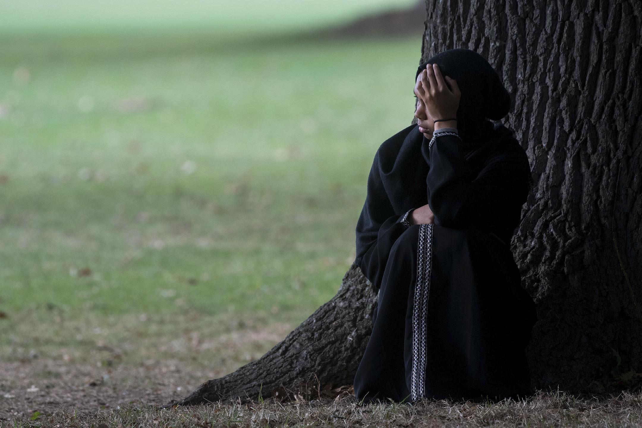 2019年3月19日,一名婦女在新西蘭基督城的Al Noor清真寺對面安靜地坐著,面對發生槍擊案現場,神情哀傷。 攝:Marty Melville/AFP/Getty Images