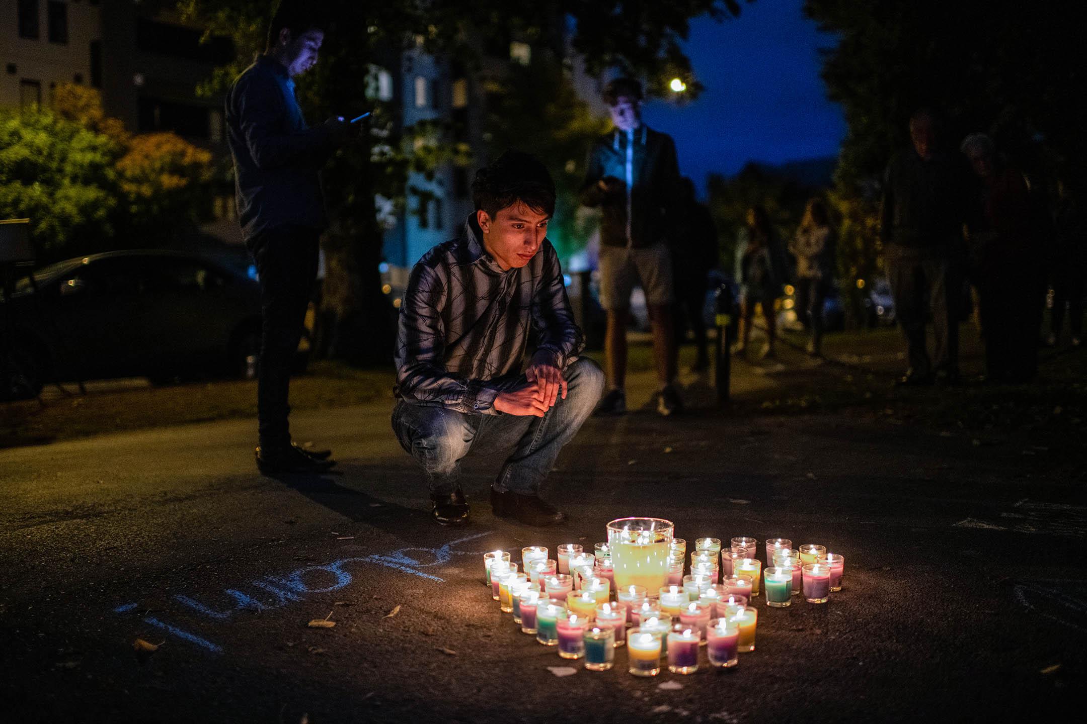 2019年3月17日新西蘭基督城,一個人在心形的蠟燭旁哀悼槍撃案的受害者。 攝:Carl Court/Getty Images