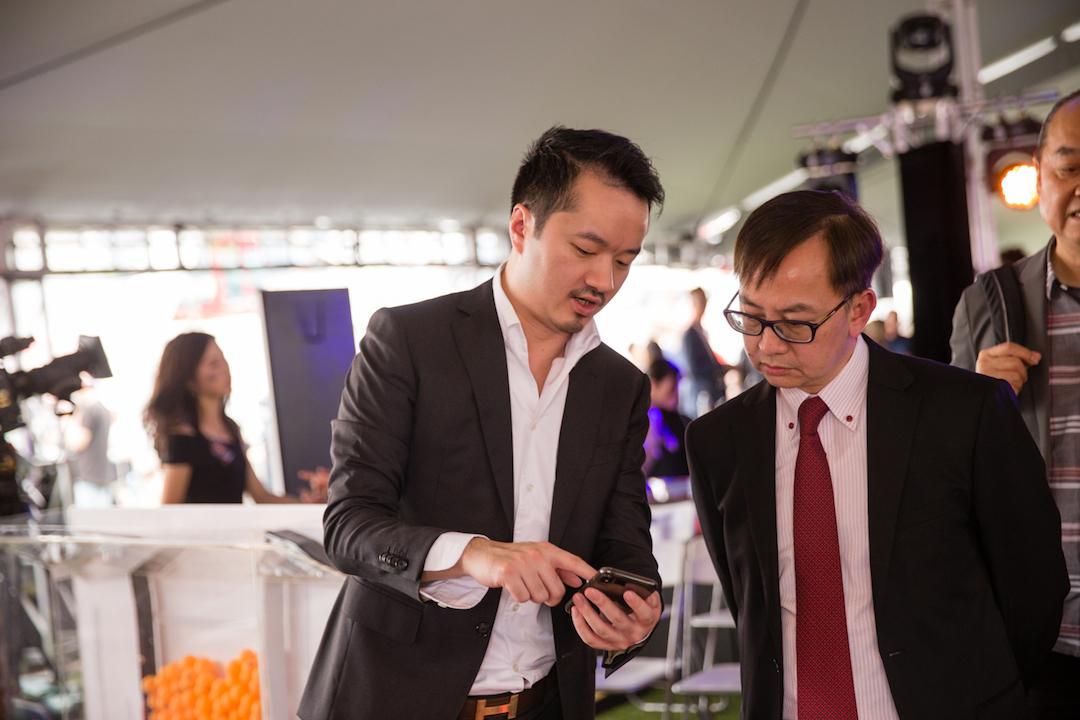 香港投杯球協會主席趙朗(左)向香港特別行政區創新及科技局副局長鍾偉強簡介如何用 app ,參與電子投杯球。