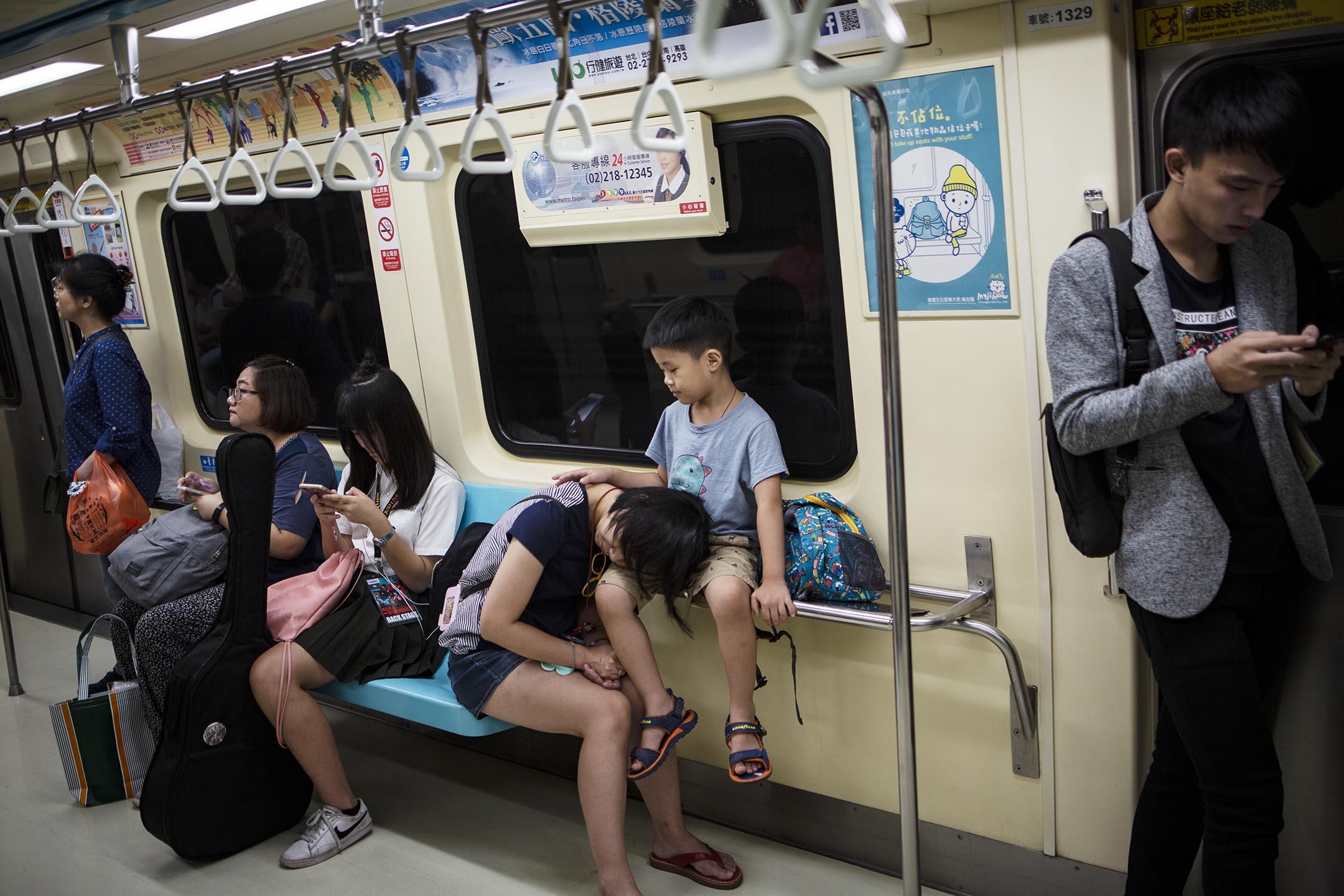 2018年9月1日,台北捷運內一個母親睡在孩子身上。 攝:陳焯煇/端傳媒