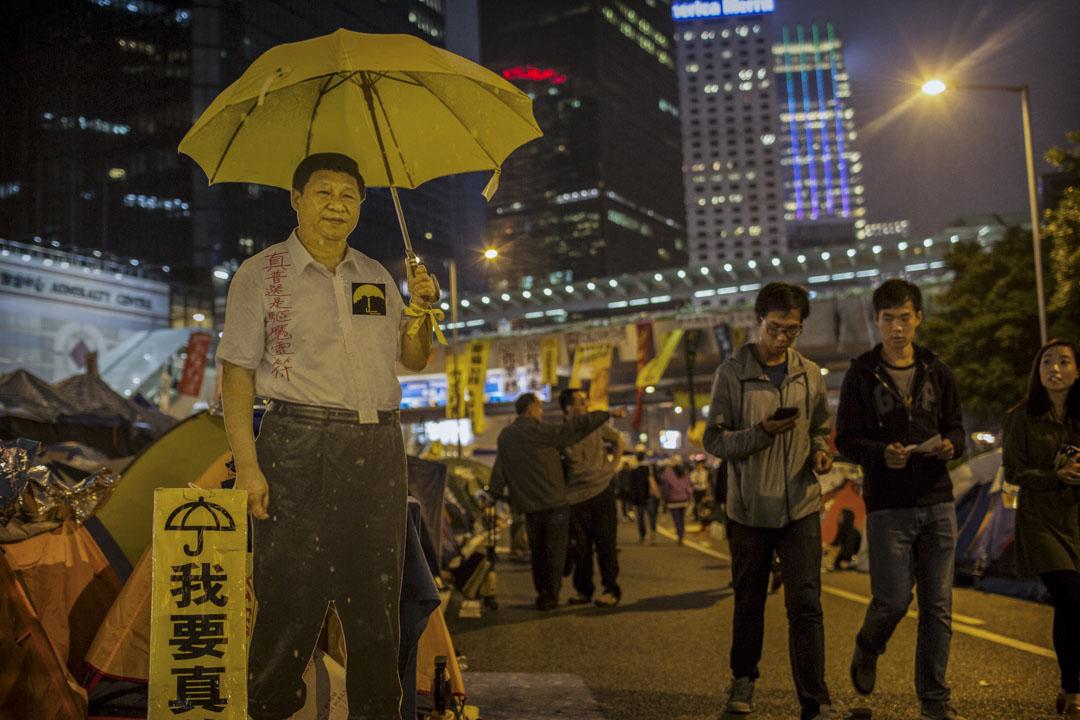 2014年11月12日,金鐘佔領現場,一幅國家主席習近平拿著一把黃色雨傘的紙牌竪立在路中央。
