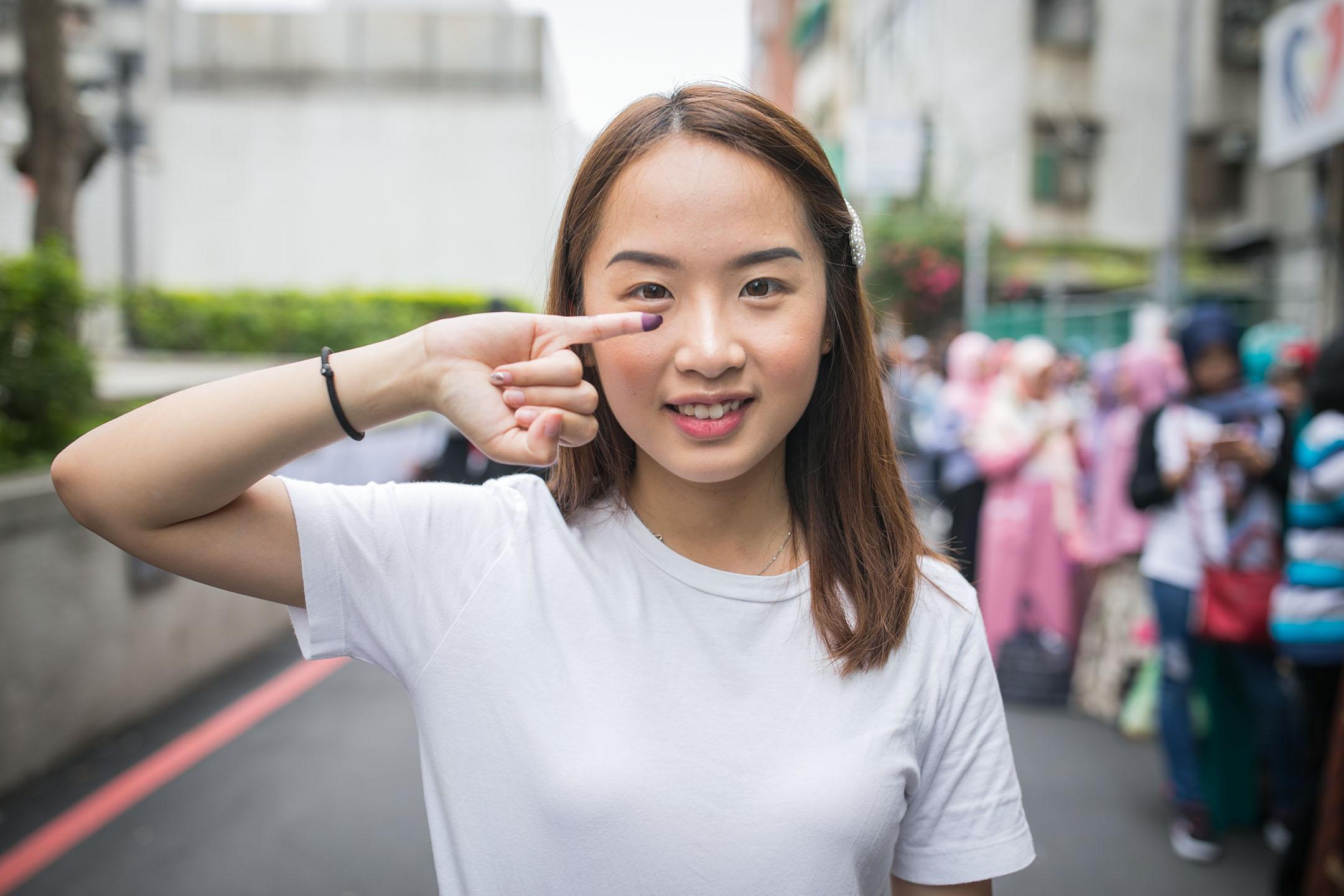 2019年4月14日,台北一處投票所外,銘傳大學印尼生林艷玲在台灣首投,為本屆印尼大選投出手中一票。 攝:陳焯煇/端傳媒