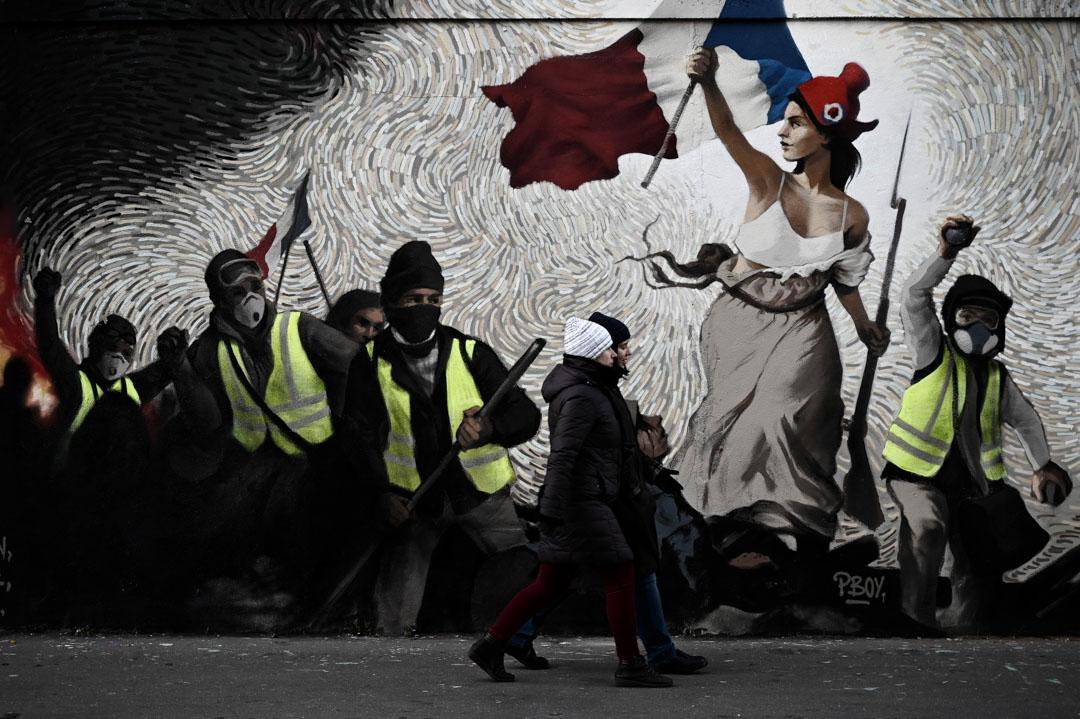 2019年1月8日,行人走過街道藝術家PBOY關於黃馬甲運動的壁畫。