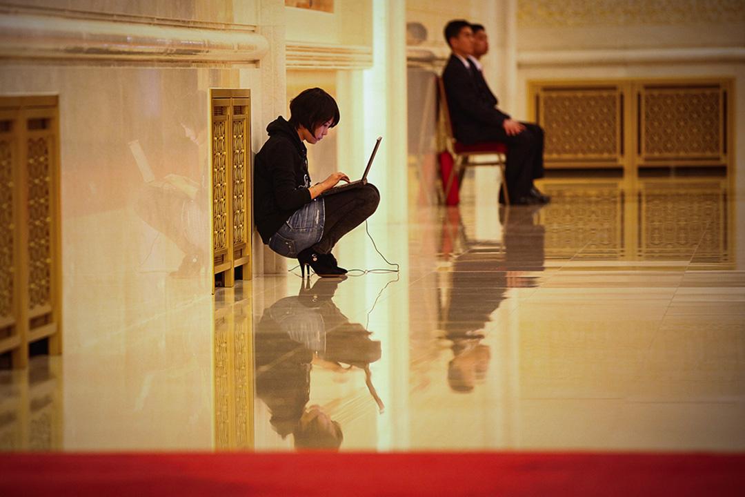 2011年3月2日,北京人民大會堂的一個新聞發布會上,記者拿著電腦工作。