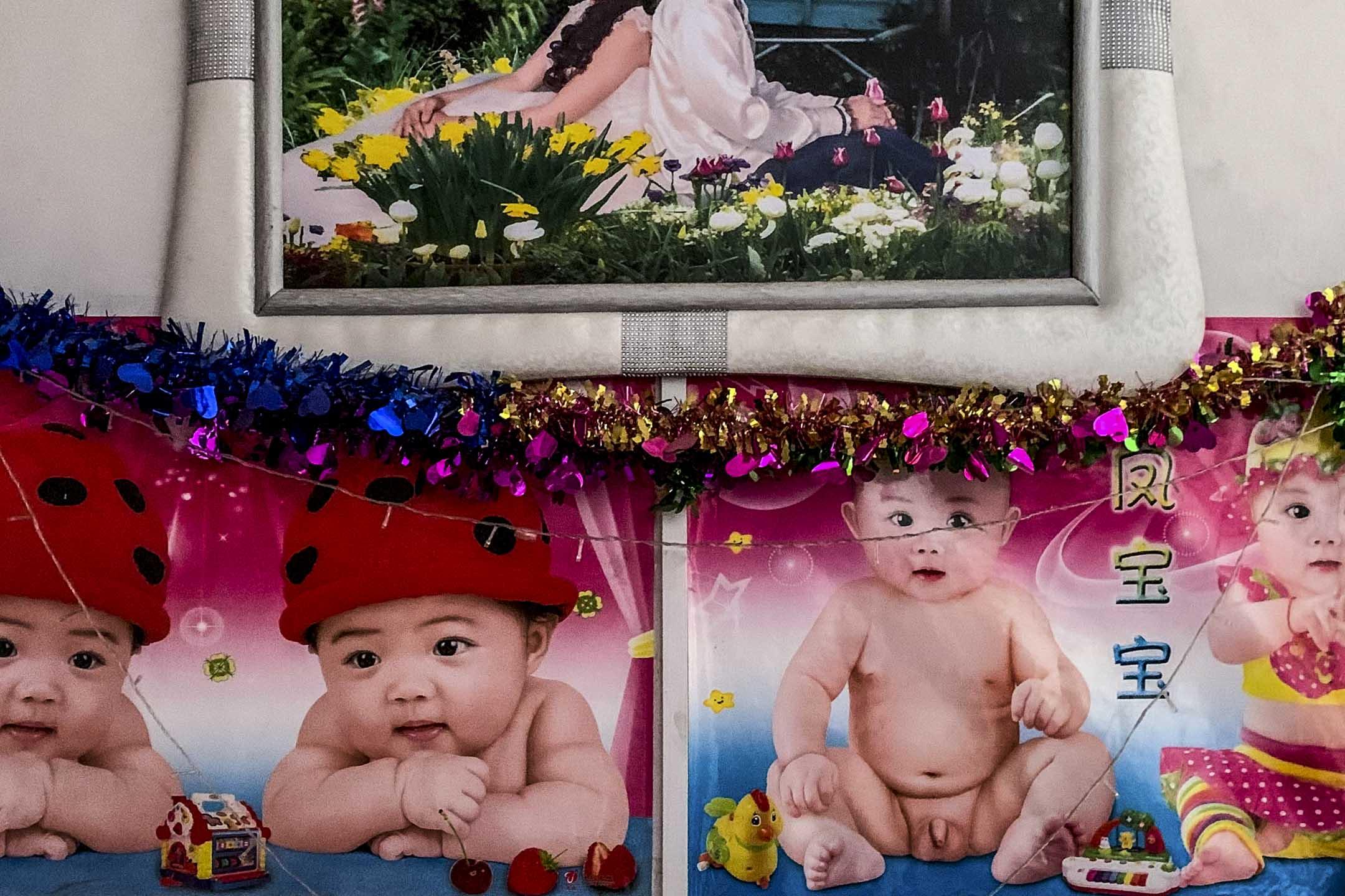 越南新娘逃跑後的第五個月,小北的臥室裏依舊掛著當初拍的結婚照。照片下的嬰兒圖片,是長輩對新婚夫婦早日「開花結果」的祝福。 攝影:阿唐