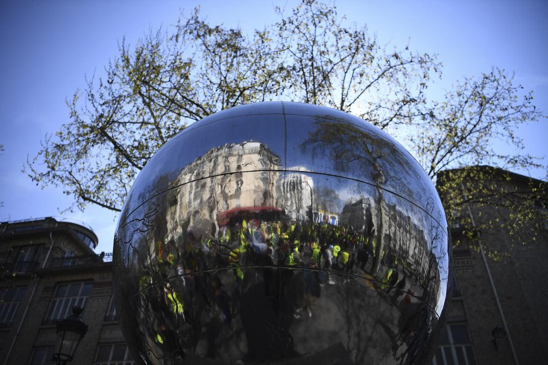 2019年4月6日,巴黎舉行連續第21週的黃馬甲運動,示威者被反映在一個球形雕塑中。 攝:Anne-Christine Poujoulat/AFP/Getty Images