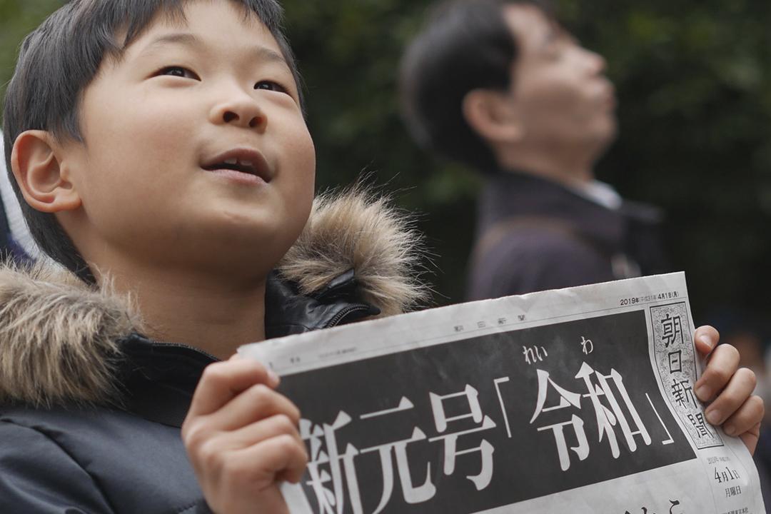 2019年4月1日,日本政府公布下月1日起改元「令和」。圖為東京一名男孩手執報導改元消息的《朝日新聞》號外。 攝:Karyn Nishimura-Poupee / AFP / Getty Images
