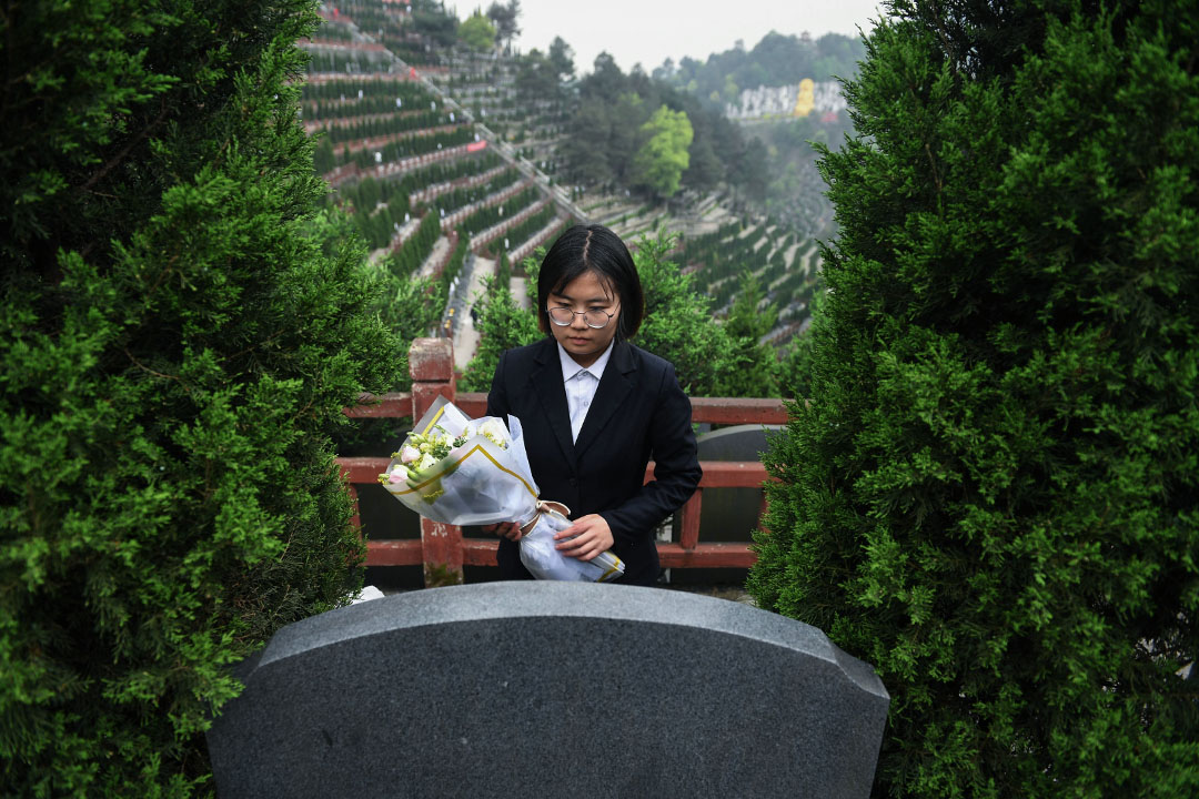 2019年4月3日,重慶市九龍坡區龍居山陵園,23歲的錢樺手捧鮮花,對着墓碑鞠躬,代客掃墓。