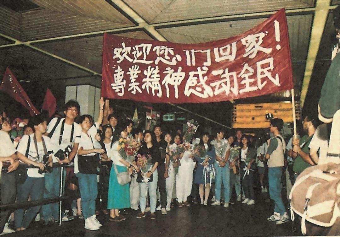 大批新聞界同業和市民在啟德機場迎接北京回港記者。