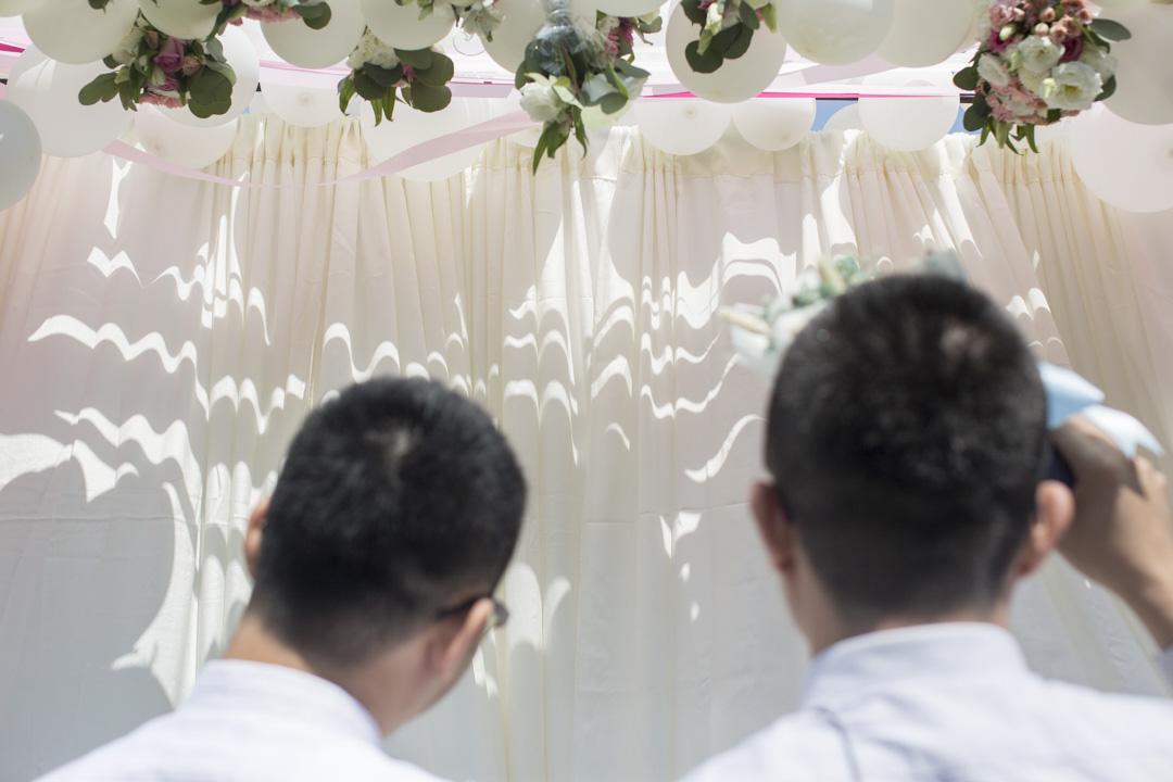 同志伴侶等候穿越幸福拱門。