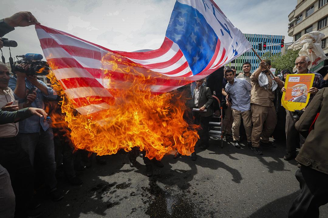 2018年5月11日,伊朗人在伊朗首都德黑蘭的示威活動中焚燒了一面美國國旗。 攝:Stringer/AFP via Getty Images