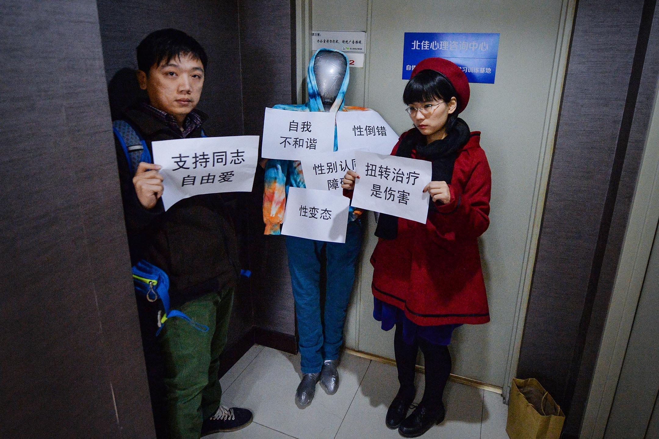 """2013年12月10日,同性戀權利組織LGBT Rights Advocacy China的負責人彭燕輝(左)在提供""""性重新定向""""服務的診所門外抗議。 攝:Mark Ralston/AFP via Getty Images"""
