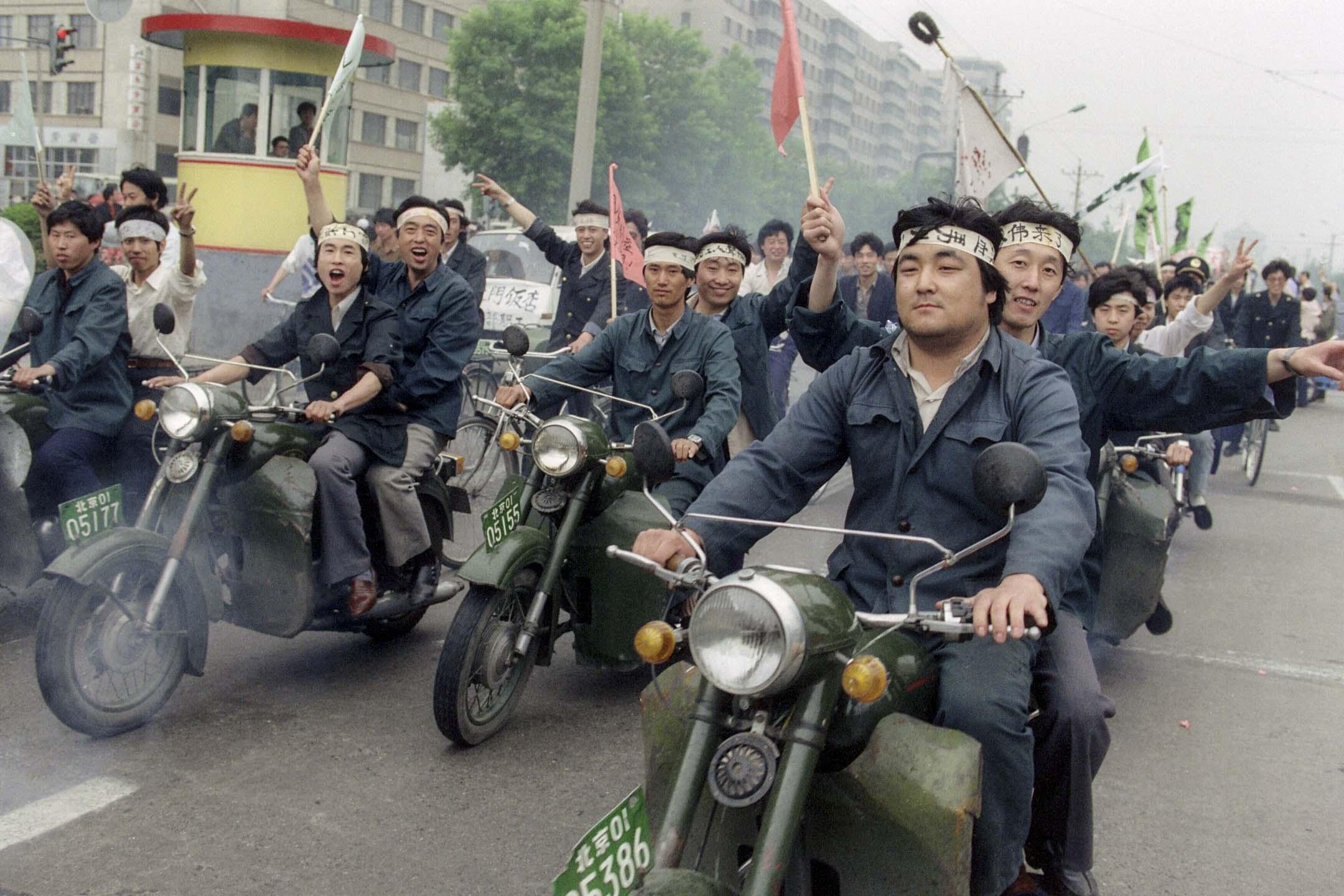 1989年5月18日,工人在北京街道以電單車遊行聲援天安門廣場絕食的學生。 攝:Catherine Henriette/AFP/Getty Images