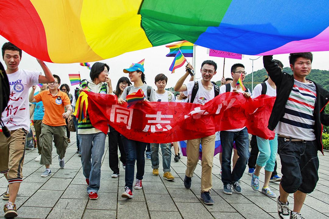 2013年5月17日,中國湖南省長沙市舉行的反歧視遊行中,年輕人舉著彩虹旗,,大約有一百人聚集在一起參加遊行。
