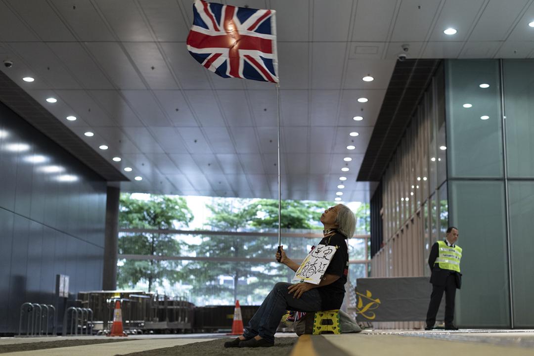 英國及加拿大發表聯合聲明,質疑《逃犯條例》修訂損害香港權利及自由,敦促港府考慮不同持份者的意見。圖為2019年5月4日,一名示威者在香港立法會外舉起英國國旗。 攝:Philip Fong / AFP / Getty Images