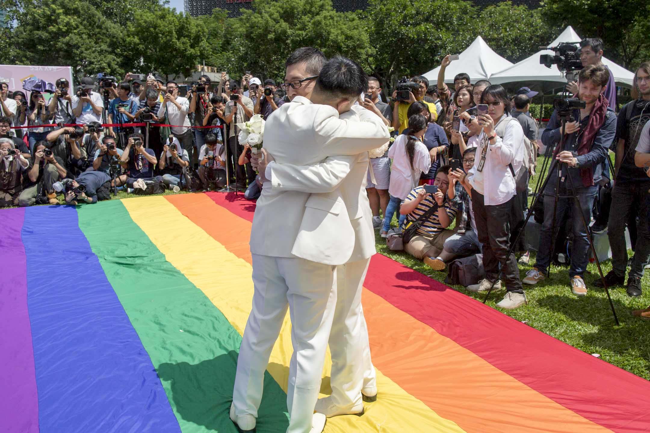 2019年5月24日,婚權平台與台北市政府民政局合辦「幸福起跑線Wedding Party」,新婚同志在彩虹旗上擁抱。 攝:林振東/端傳媒