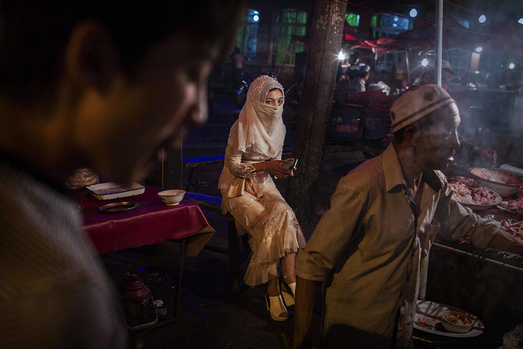 2014年8月1日,中國新疆維吾爾自治區喀什市,一位維吾爾婦女坐在地方市場內的食物攤檔。 攝:Kevin Frayer/Getty Images