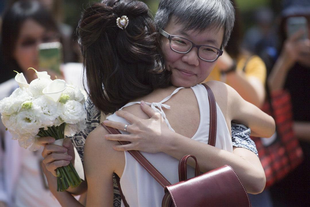 同志伴侶在戶外婚禮派對上擁抱。