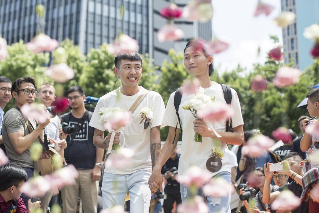 完成結婚登記的同志伴侶穿越幸福拱門踏上彩虹地毯,接受祝賀。