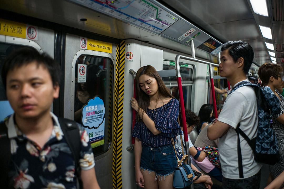 2016年7月18日,乘客在香港地鐵列車中睡覺。 攝:Anthony Wallace/AFP via Getty Images