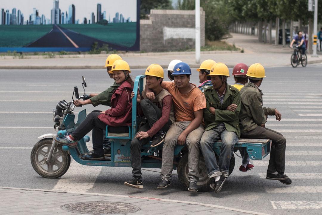 2017年6月13日,年輕工人乘坐機動三輪車前往北京郊區昌平的一處建築工地。