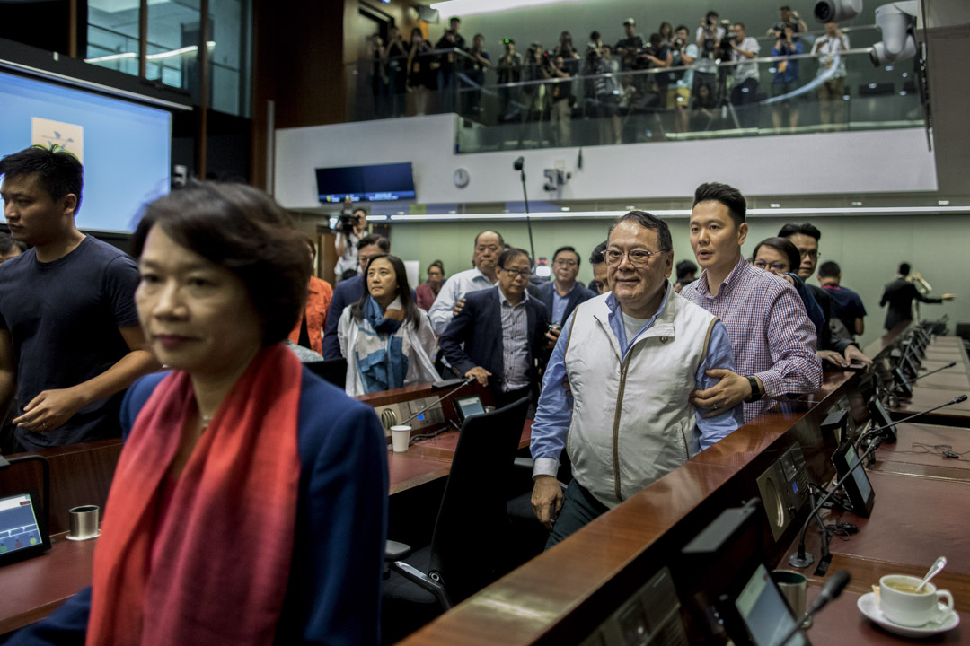 12:02PM - 經民聯議員石禮謙在數名建制派議員護送下離開會議室。
