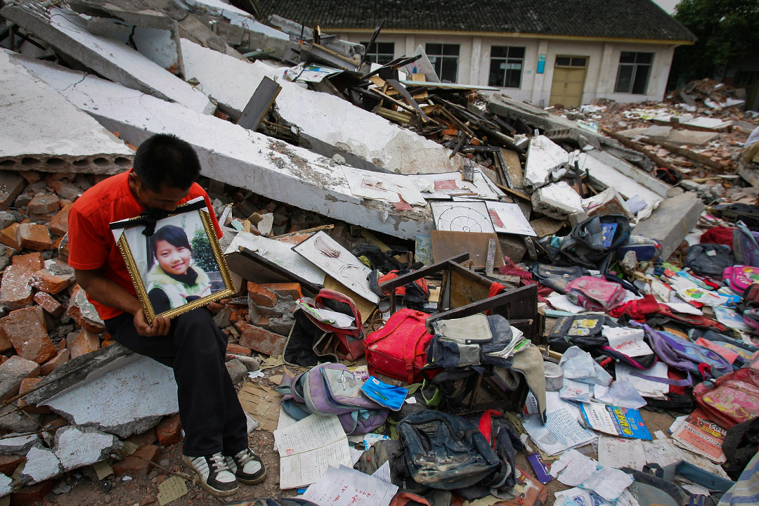2008年5月20日,四川省綿竹市的學校,一名父親參加一場哀悼和抗議活動,其女兒在地震因校舍倒塌而壓死。