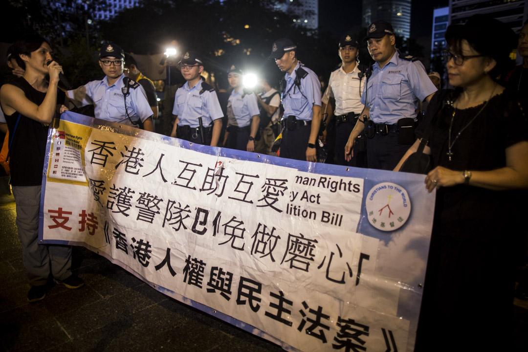 社工呂智恆拿著「支持香港人權民主法案」的橫額,要求成立獨立調查委員會以還警方清白, 期間曾與參與集會者推撞, 及後在警方護送下離去。