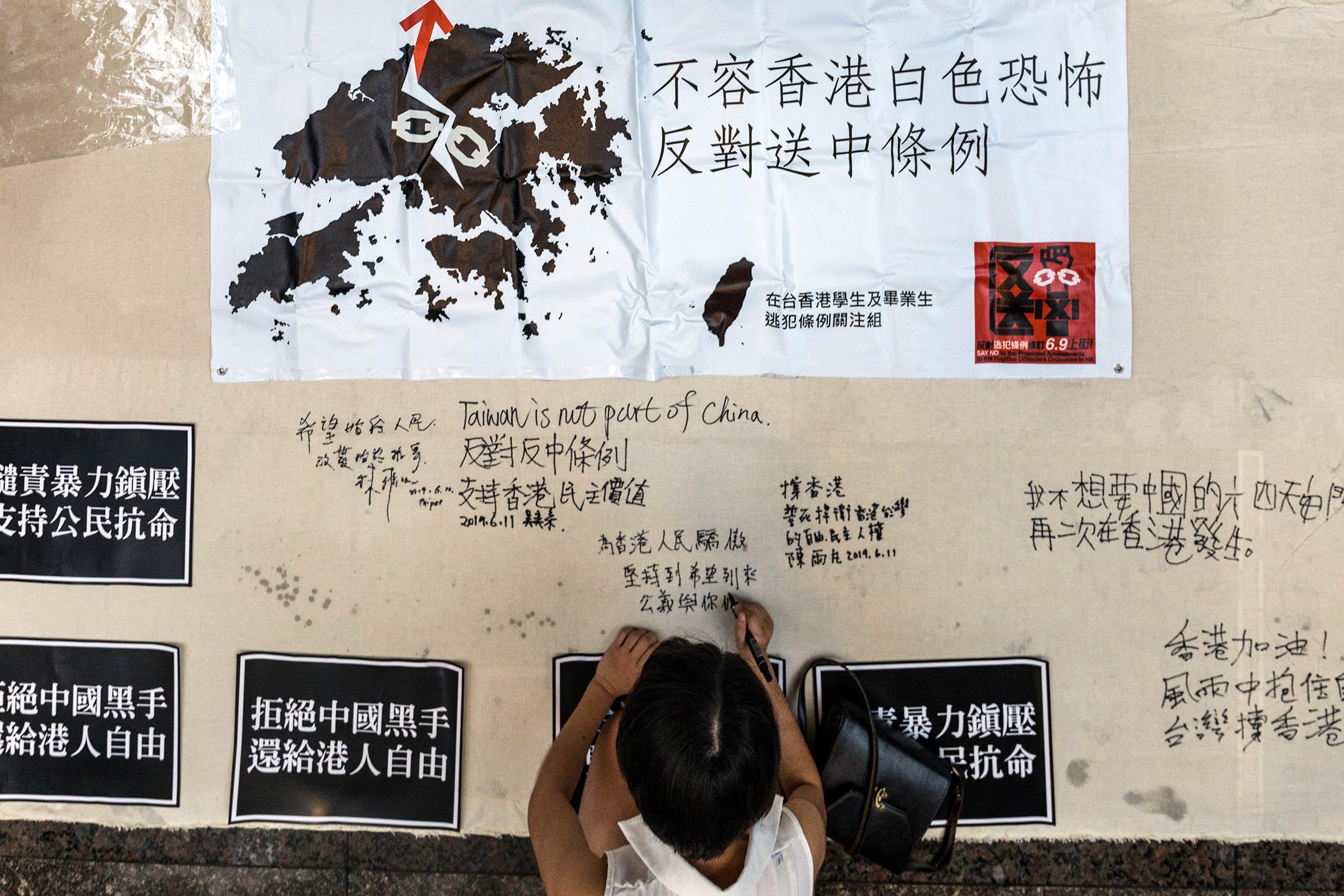 2019年6月10日,約莫30名台港青年出席「台灣青年挺香港,堅決抗議反送中」記者會, 記者會結束後,多名香港學生紛紛在主辦方帶來的白布寫上聲援香港的話語。 攝:陳焯煇/端傳媒
