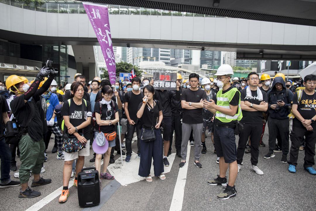 2019年6月15日,警方派出談判專家與群眾溝通時,社工許麗明與陳虹秀(中)輪流持麥克風,協助在場人士表達意見。