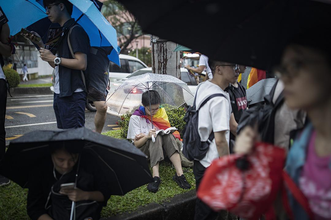 2019年5月17日,台北立法院外挺同團體發起集會,參加者在大雨下舉傘等候投票結果,一名支持者在看書。